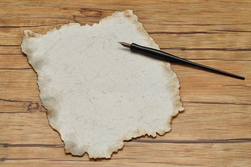 Svart reservoarpenna för tappning och ett stycke av gammalt papper royaltyfri bild