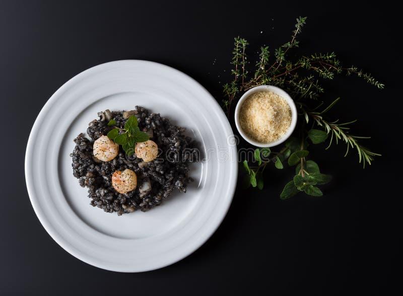 Svart risotto med örter och parmesan arkivbild