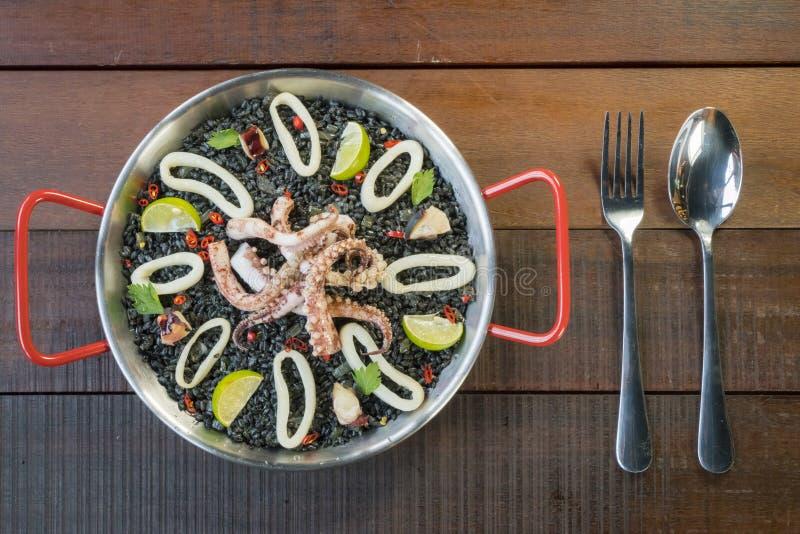Svart risotto med tioarmad bläckfisk- och färgpulversås arkivbild