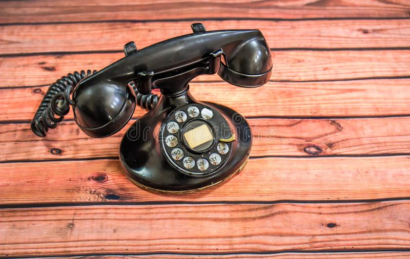 Svart roterande telefon för Retro tappning på skeva träSlats royaltyfri fotografi