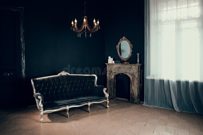 Svart rum i slotten med ett fönster, en ljuskrona, en soffa och en spegel och spis arkivbild
