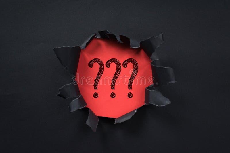 Svart sönderriven pappers- avslöjande frågefläck på rött papper arkivbild