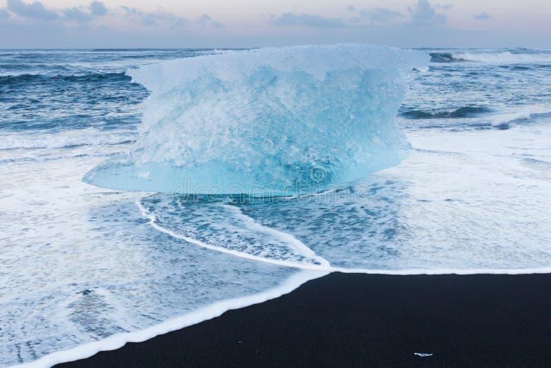 Svart sandstrand med is som bryter från glaciären, Island royaltyfri foto