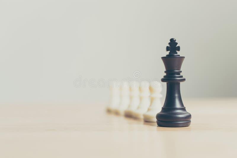 Svart schackdiagram som leder vitt schack på trätabellen, framgång av arkivbilder