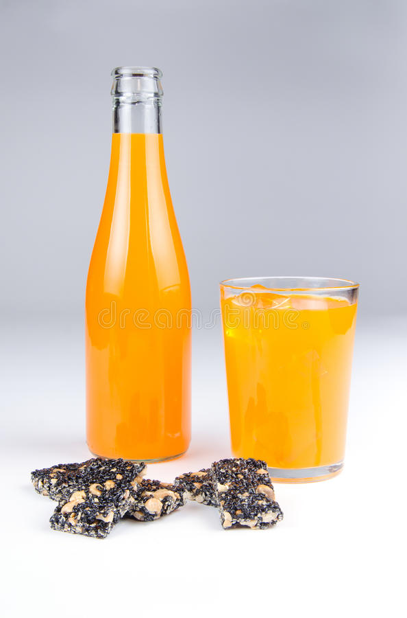 Svart sesamstång och orange fruktsaft arkivbild
