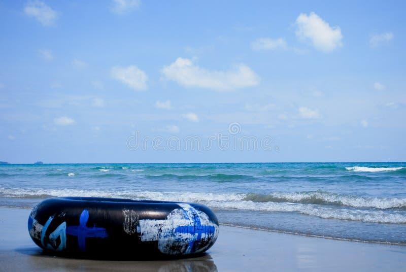 Svart simningcirkel eller inre rör på den sandiga stranden royaltyfri bild