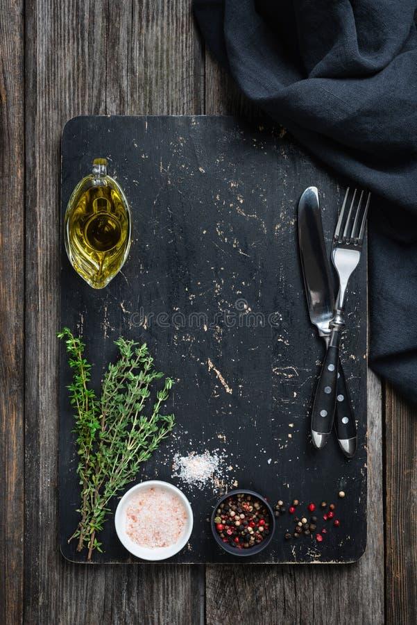 Svart skärbräda, kryddor och bestick arkivfoto