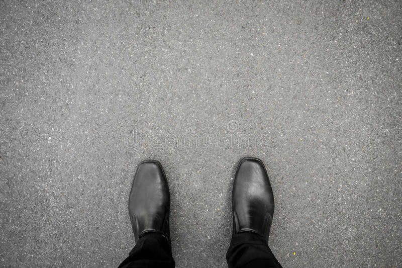 Svart skor anseende på golvet arkivfoton