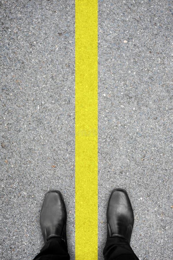 Svart skor anseende på golvet och den gula linjen arkivbild