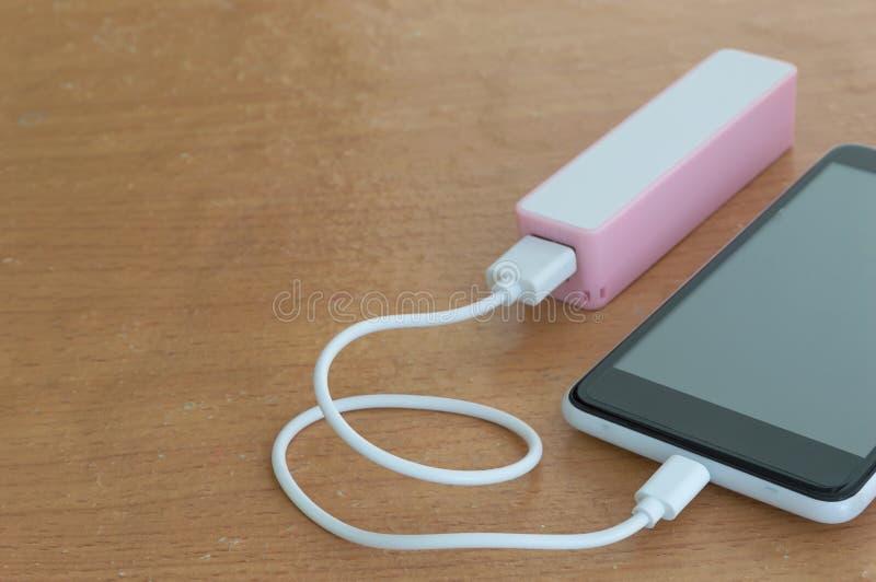 Svart smartphone med powerbank på det wood skrivbordet arkivfoton