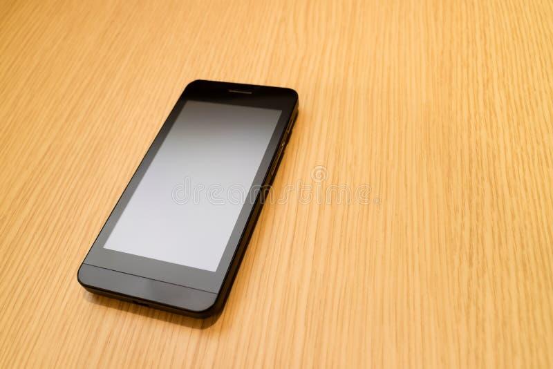 Svart smartphone på trätabellbakgrund med kopieringsutrymme för royaltyfri bild