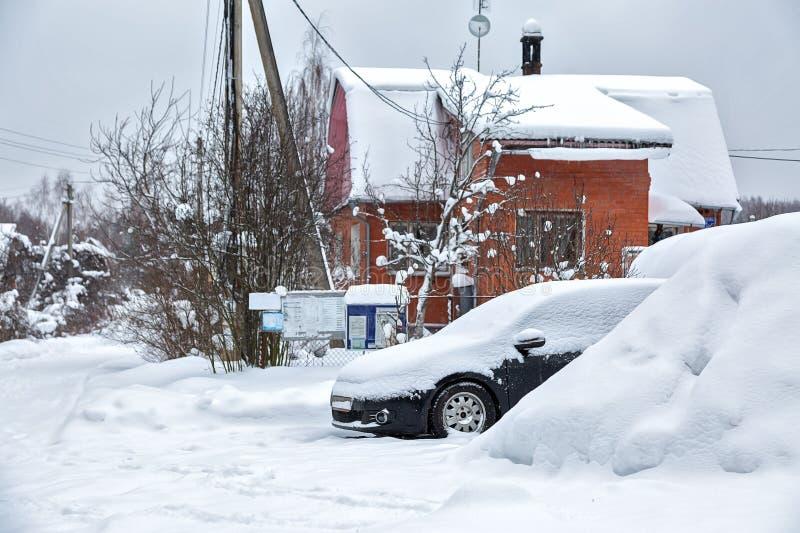 Svart smutsig bil under snön Drivor ovanför bilen tunga snowfall Djupfryst bil i snödriva vinterproblem som startar motorn arkivfoton