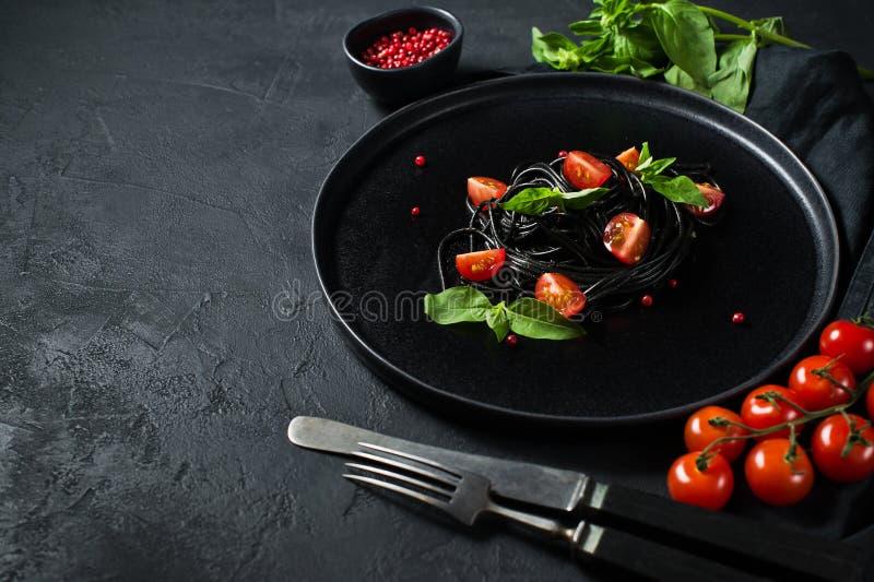 Svart spagetti med basilika och k?rsb?rsr?da tomater, vegetarisk pasta Svart bakgrund, b?sta sikt, utrymme f?r text arkivfoto