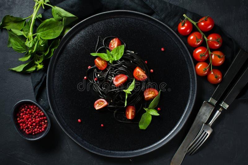 Svart spagetti med basilika och k?rsb?rsr?da tomater, vegetarisk pasta Svart bakgrund, b?sta sikt, utrymme f?r text arkivbild