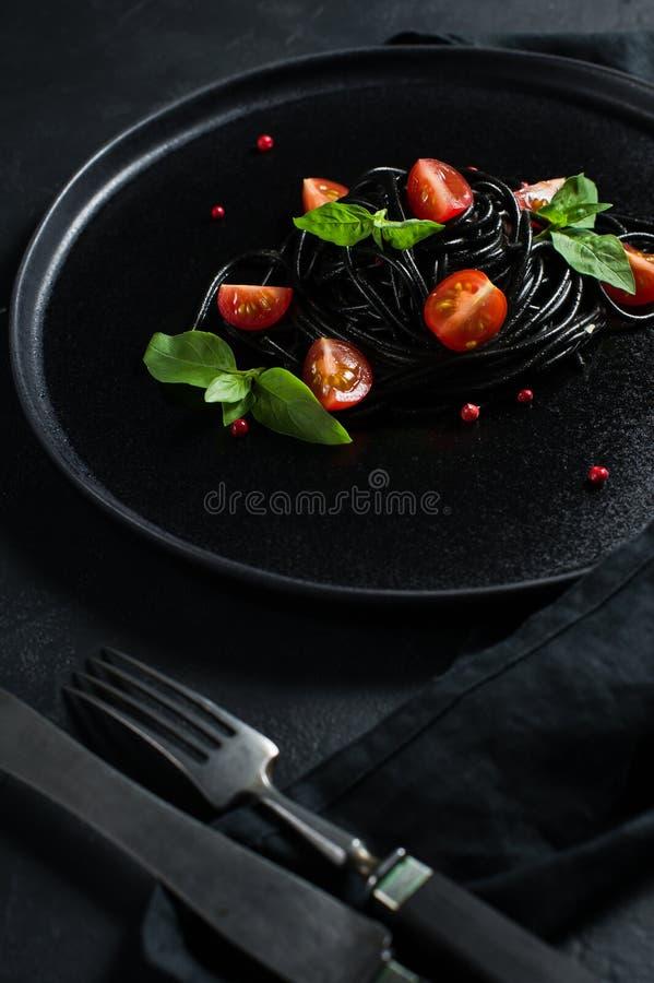 Svart spagetti med basilika och k?rsb?rsr?da tomater, vegetarisk pasta Svart bakgrund, b?sta sikt, utrymme f?r text arkivbilder