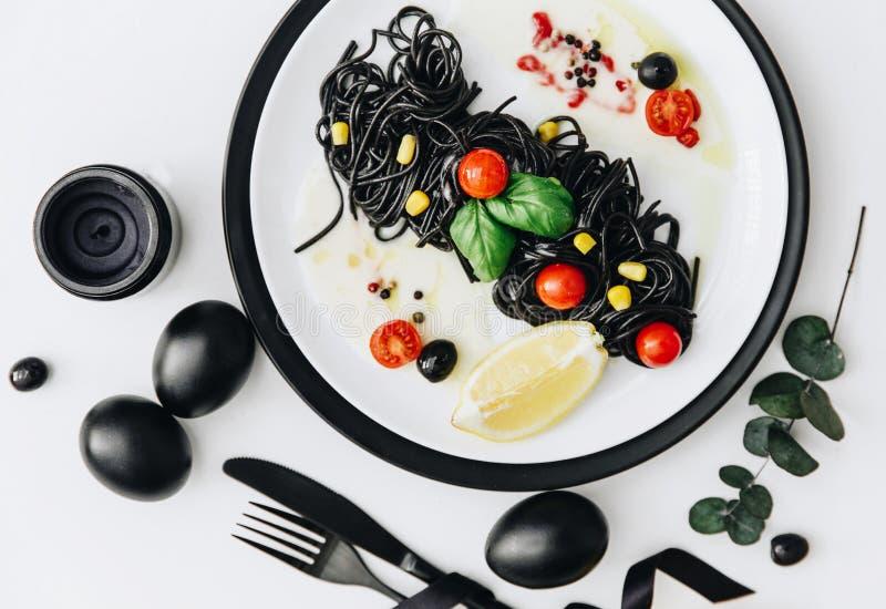 Svart spagetti med basilikan och tomater på tabellen arkivbilder
