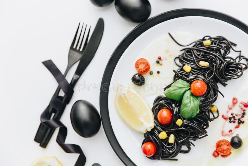 Svart spagetti med olivolja, tomater royaltyfri fotografi