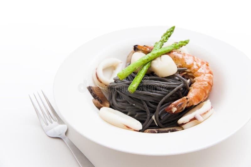Svart spagetti med skaldjur på vit bakgrund royaltyfri fotografi