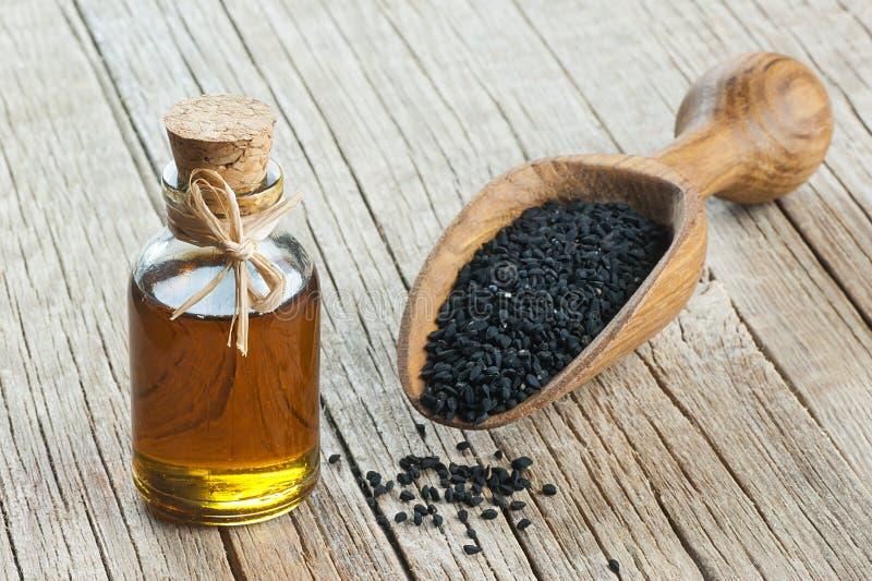 Svart spiskumminfrö och nödvändig olja med bunken och träskyffel eller sked royaltyfria foton