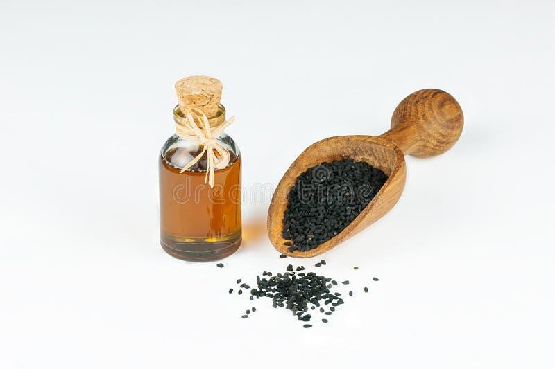 Svart spiskumminfrö och nödvändigt exponeringsglas av olja med den träskyffeln eller skeden som isoleras på vit bakgrund royaltyfria foton