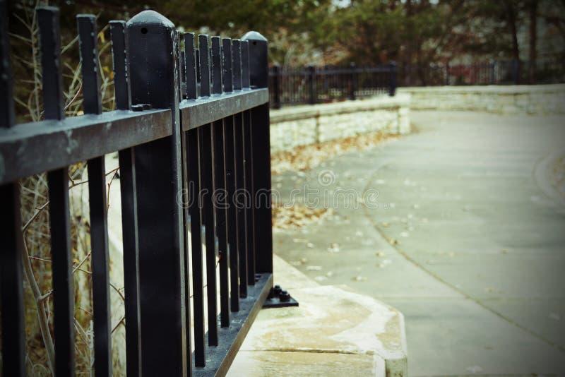 Svart staket längs en väg arkivbilder