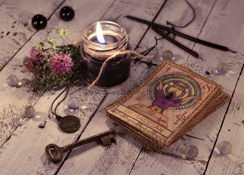 Svart stearinljus och gamla tarokkort på träplankor royaltyfri foto