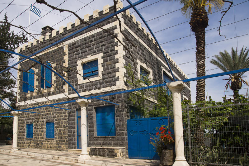Svart stenhus med blåa fönster fotografering för bildbyråer
