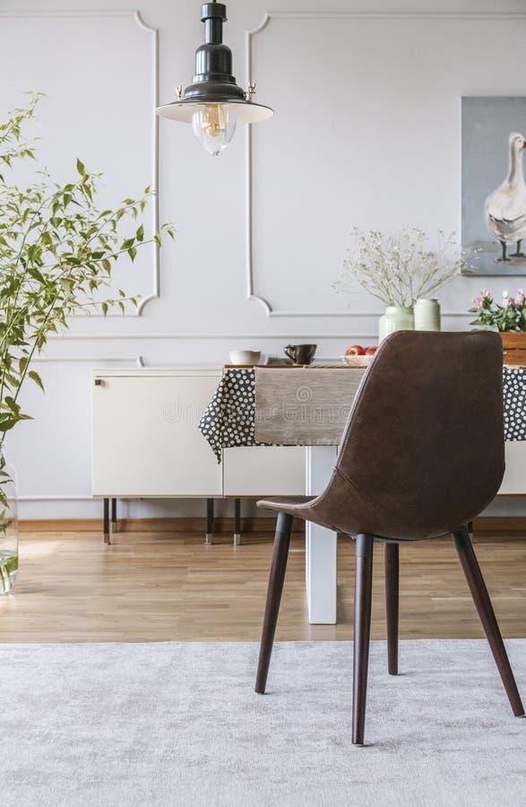 Svart stol på grå färger mattar på tabellen i matsalinre med lampan och väggen med stöpningen Verkligt foto arkivfoton