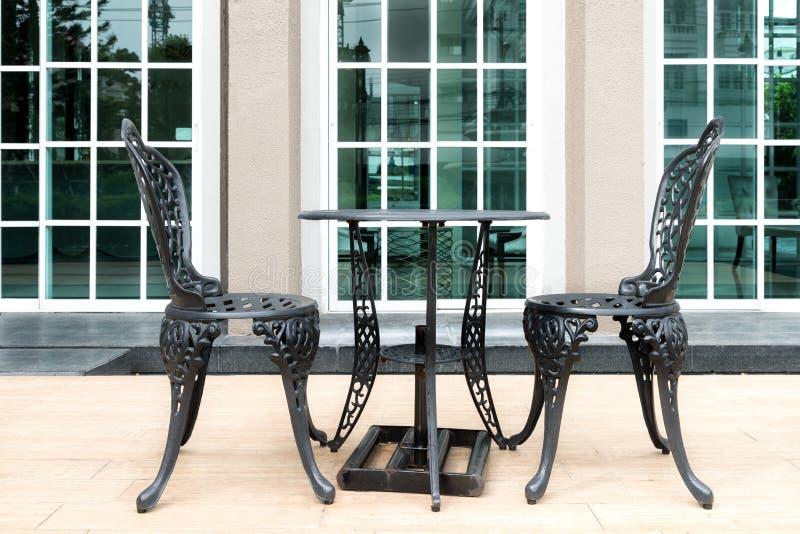 Svart stol på uteplats i europeiskt stilhus Utomhus- hus arkivbilder