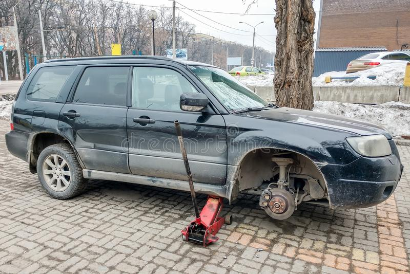 Svart Subaru skogvaktare utan ett hjul lyft p? st?lar Utbytning p? gummihjulservicemitten royaltyfria bilder