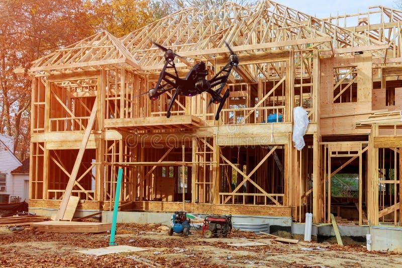 Svart surrquadcopter med kameran som flyger över konstruktion för familjhem - bygga ett nytt trä inramade huset arkivbilder