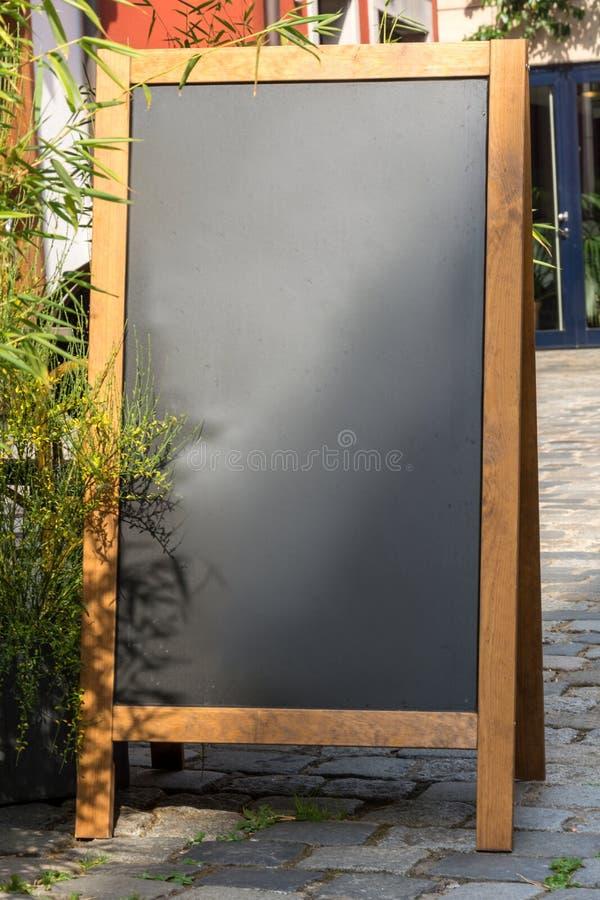 Svart svart tavlaställning på trä för en restaurangmeny i stren royaltyfri foto
