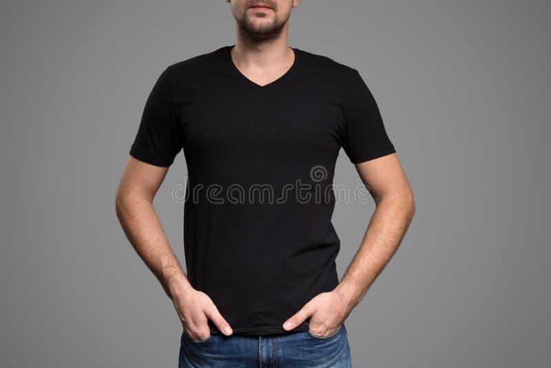 Svart t-skjorta på en mall för ung man Grå färgbakgrund royaltyfri foto