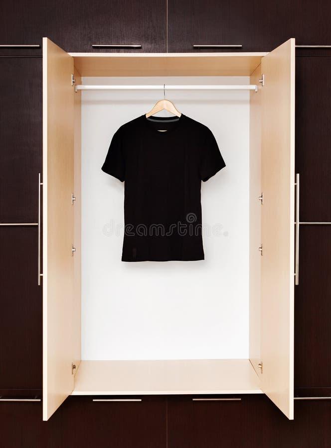 Svart T-tröja på trähängare i en garderob arkivfoton