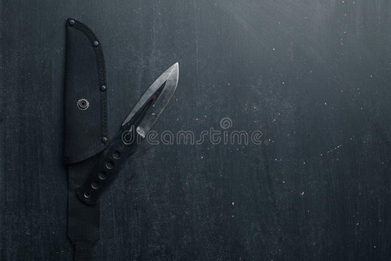 Svart taktisk kniv på svart bakgrund militär arkivbild