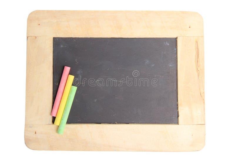 Svart tavla för kopieringsutrymme med färgrika stycken av krita på vit bakgrund arkivbild