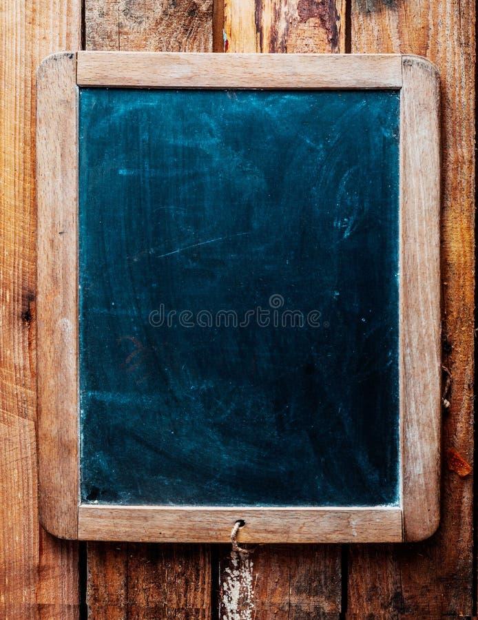 Svart tavla för tappning över wood bakgrund. royaltyfria foton