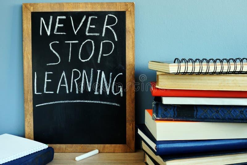 Svart tavla med aldrig stoppar att lära och böcker arkivbild