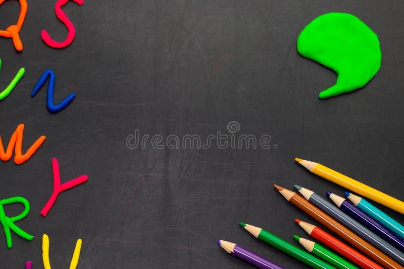 Svart svart tavla med färgrika blyertspennor och bokstäver, begrepp för royaltyfri foto