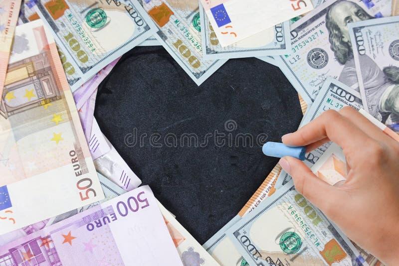 Svart tavla med hjärtaform från kassa oss dollar och eurosedlar med kopieringsutrymme som sätter in text arkivbild