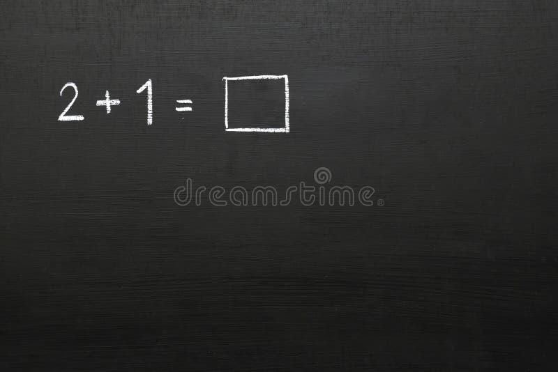 Svart tavla med matematikproblem Nummer och matematiska symboler u royaltyfri foto