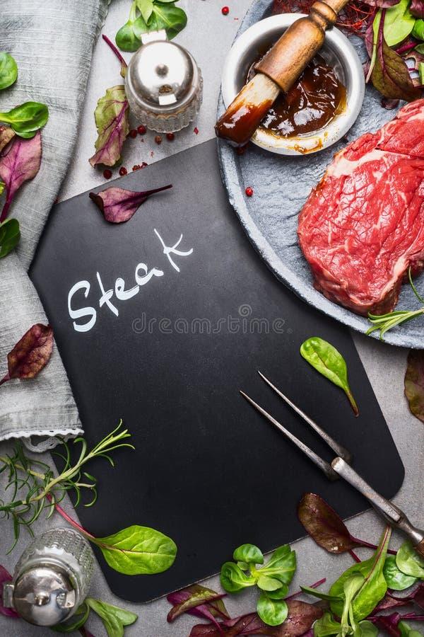 Svart tavlamatlagningbakgrund med rå biff, köttgaffeln, ny smaktillsats och marinerar, den bästa sikten arkivfoton