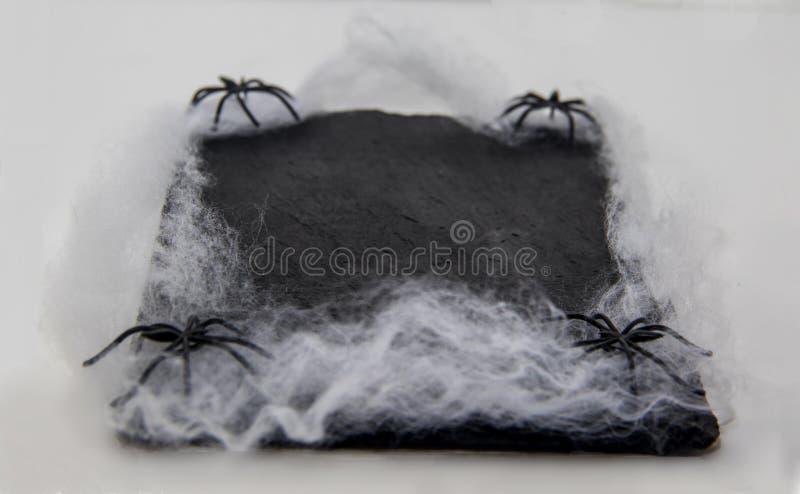 Svart tavlamaträtt som dekoreras med spindlar och spindelrengöringsduken för halloween royaltyfri fotografi