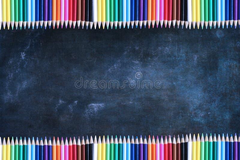 Svart tavlatexturbakgrund med rader av kulöra blyertspennor arkivfoton