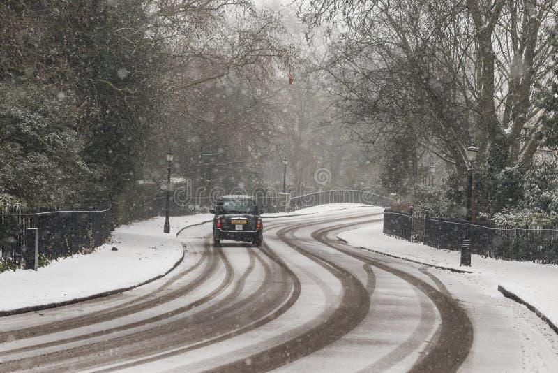 Svart taxi i vintervit London royaltyfri fotografi