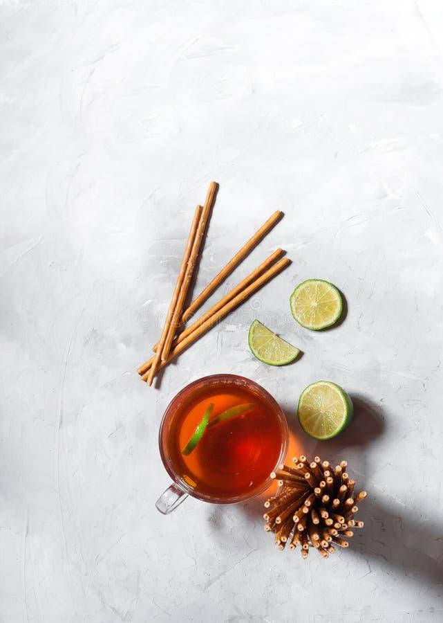 Svart te i ett exponeringsglas rånar med limefruktskivor p? en gr? f?rgbakgrund fotografering för bildbyråer