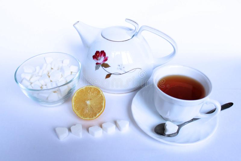 Svart te med citronen i den vita koppen på vit bakgrund Slapp fokus royaltyfria foton