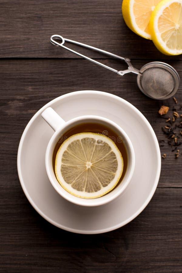 Svart te med citronen på en träbakgrund fotografering för bildbyråer