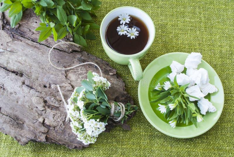 Svart te på en bakgrund av gröna textiler, en bukett av blommor arkivbild