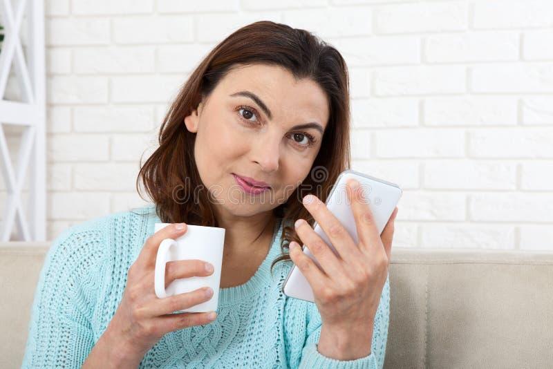 svart telefon för kommunikationsbegreppsmottagare Attraktiv kvinna som ser hennes smarta telefon och ler, medan sitta på soffan h royaltyfri foto